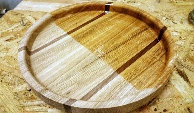 Покрытие круглого деревянного подноса защитным маслом